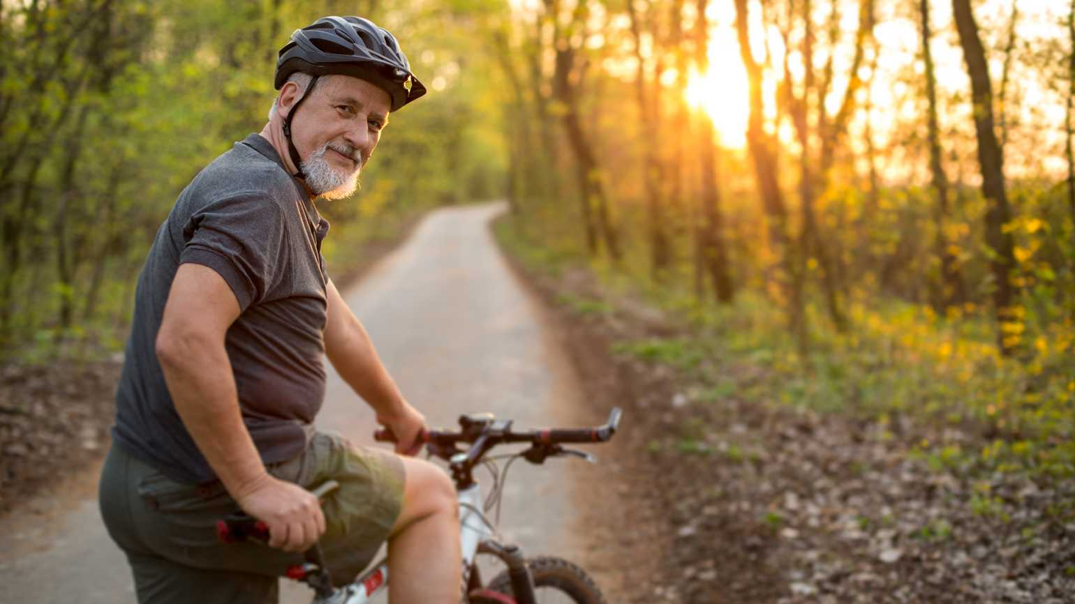 An older man getting ready for a morning bike ride in the woods.