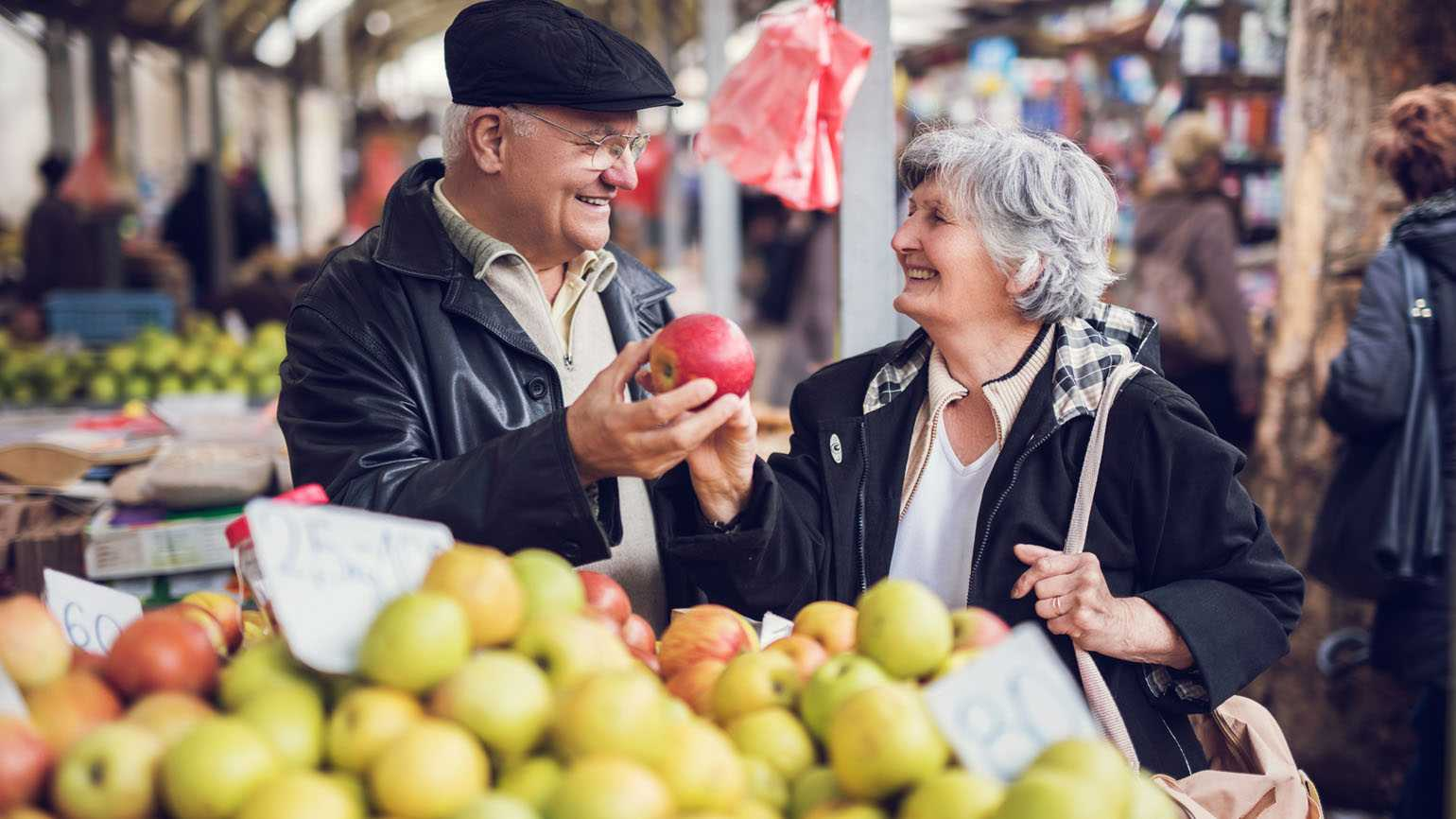 A couple in their golden years shopping at the farmer's market.