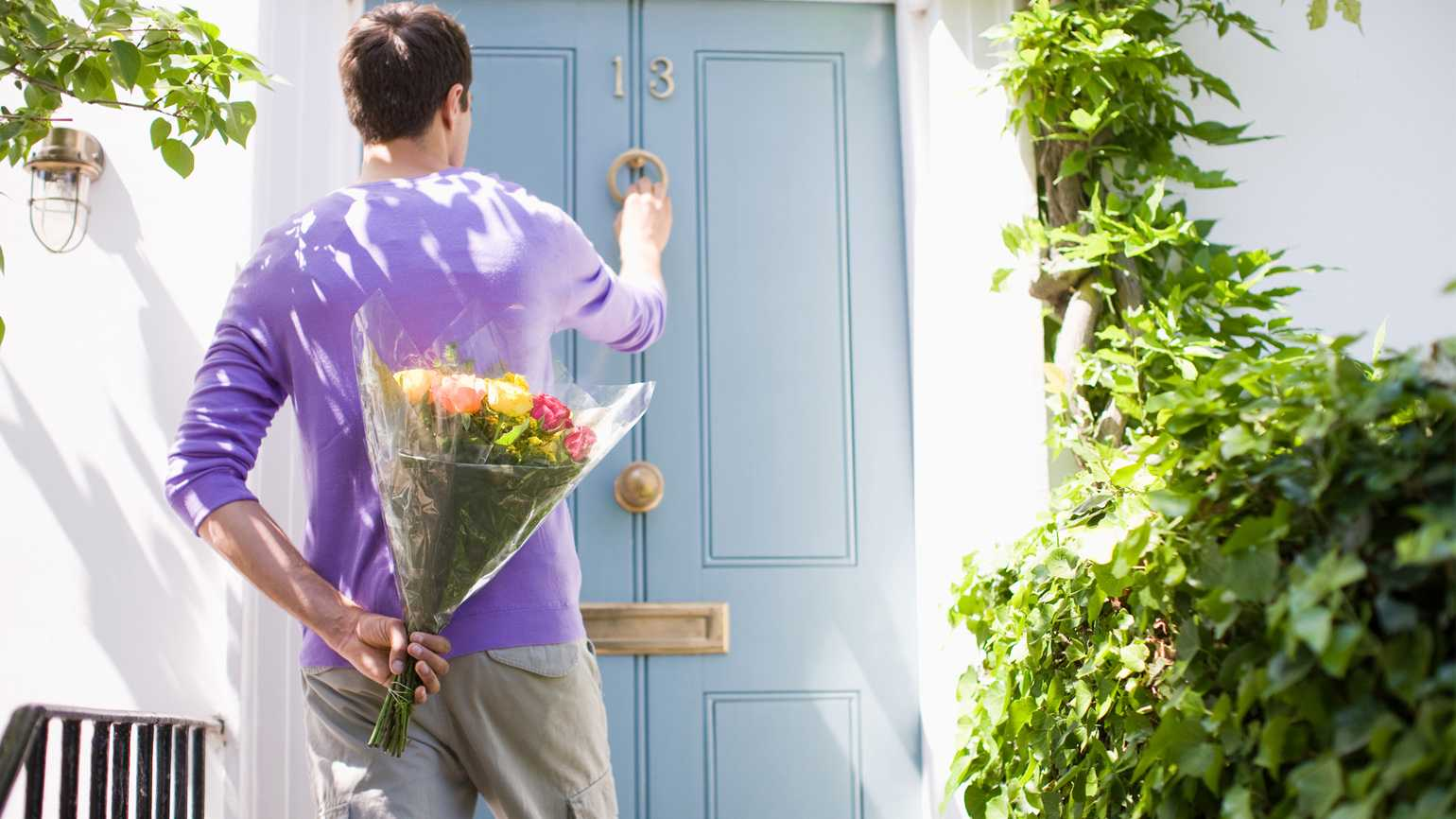 A man knocking on a door with a bouquet of flowers behind his back on a Spring day.