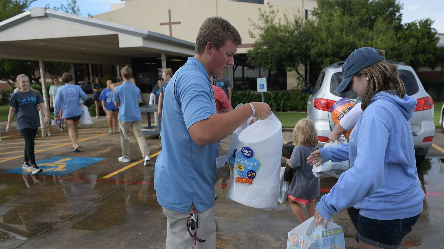 A volunteer receives donated items outside of a shelter for volunteer rescue workers set up at the Fairfield Baptist Church