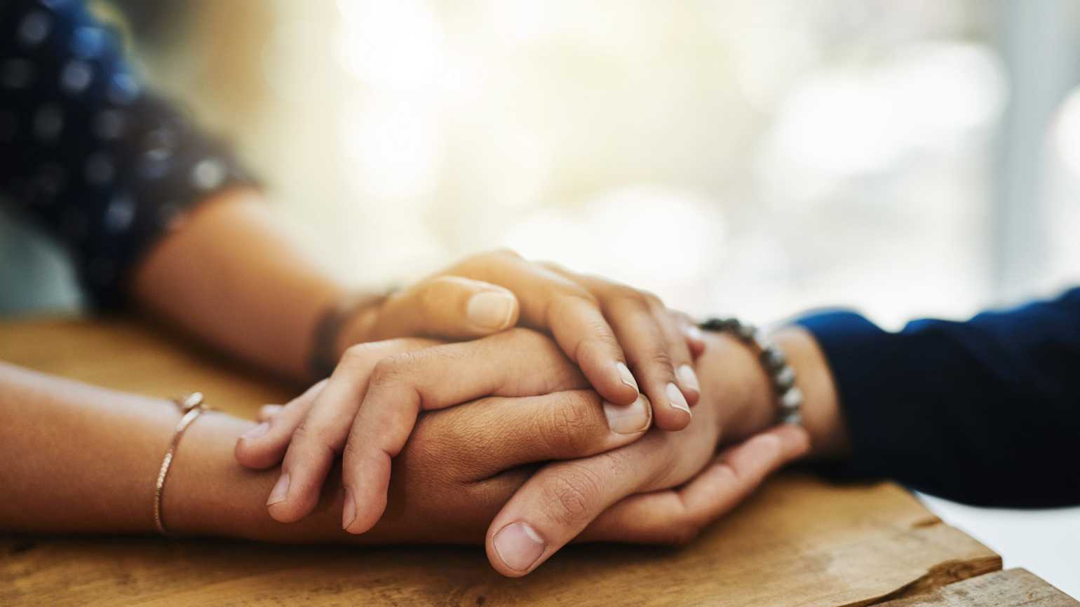 Closeup shot of two unrecognizable people holding hands in comfort.