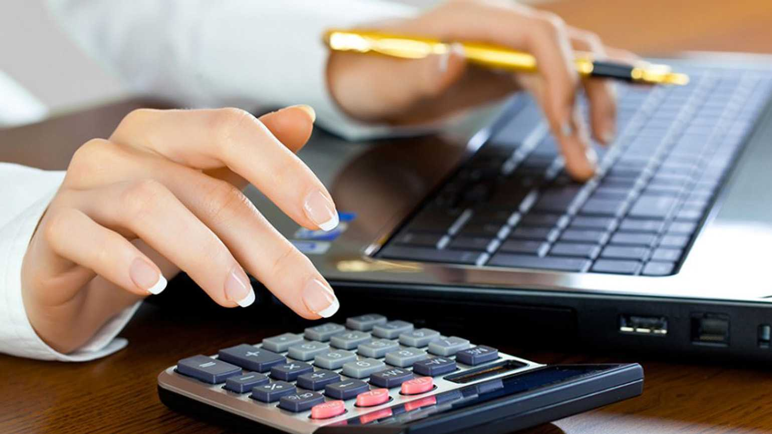 A woman calculating costs using a calculator and laptop.