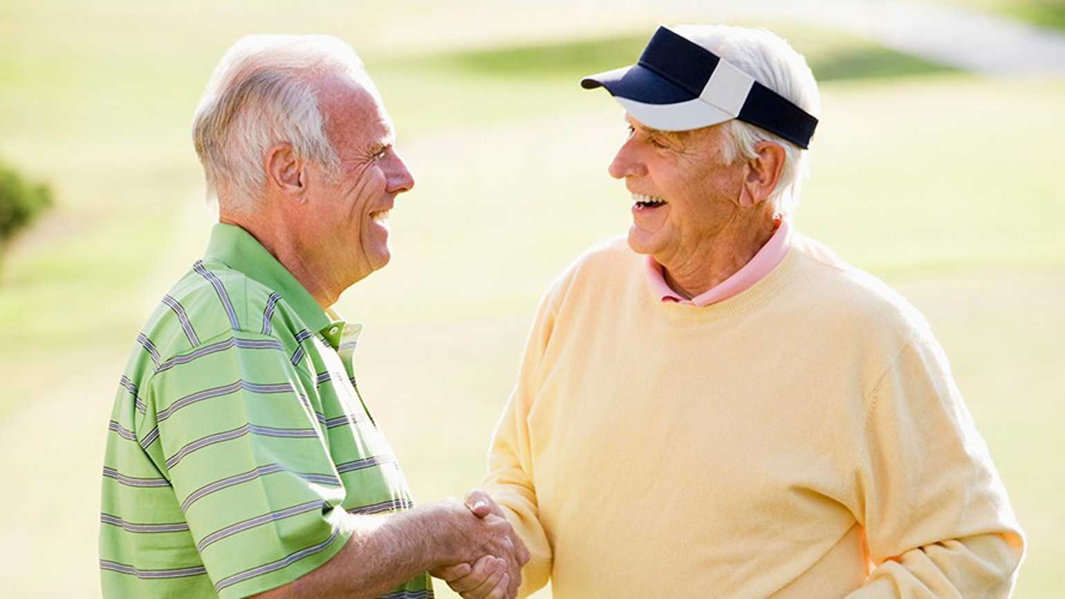 Two men conversing on a golf course.