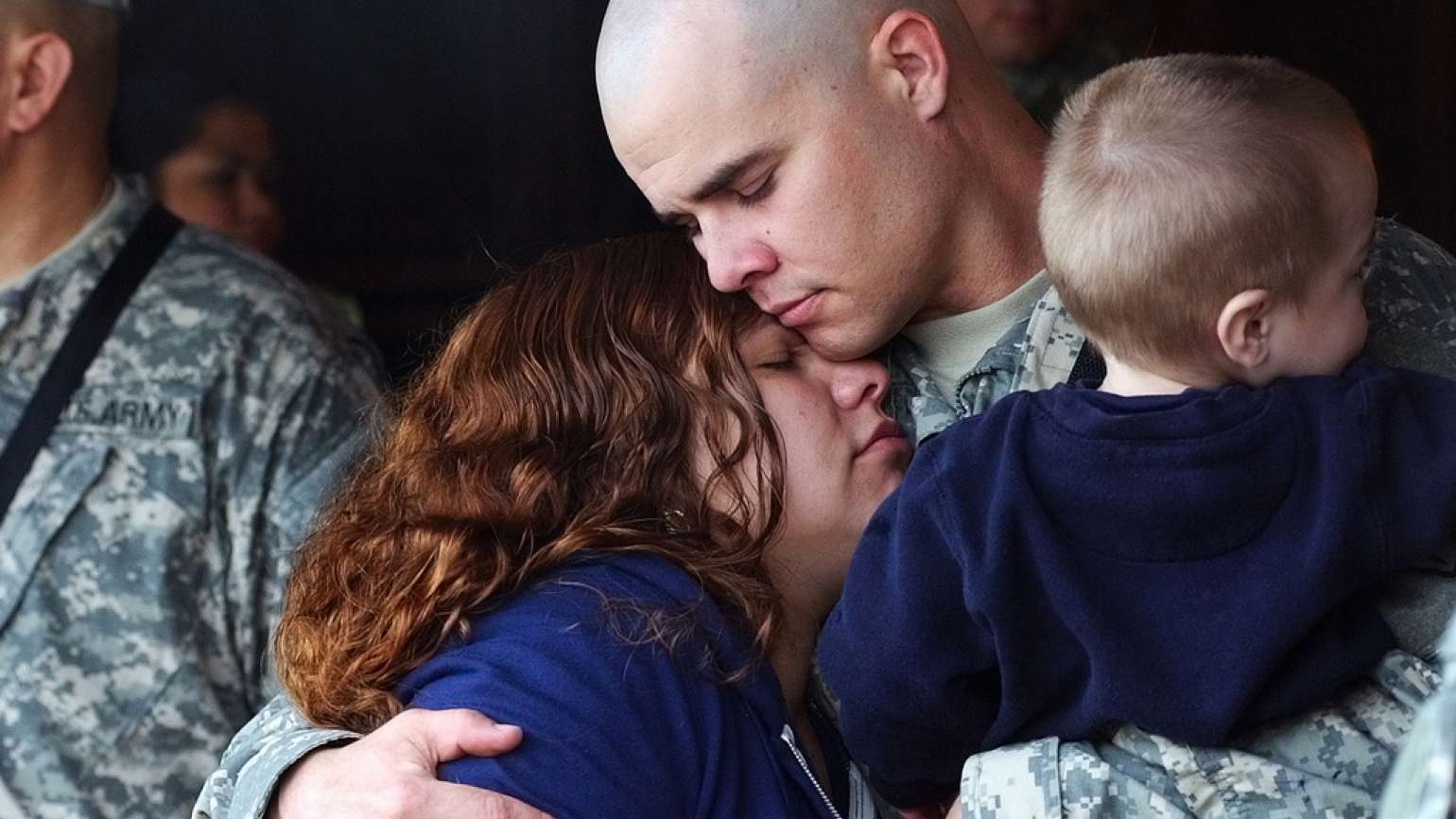 Guideposts: A soldier in fatigues hugs his wife and child.