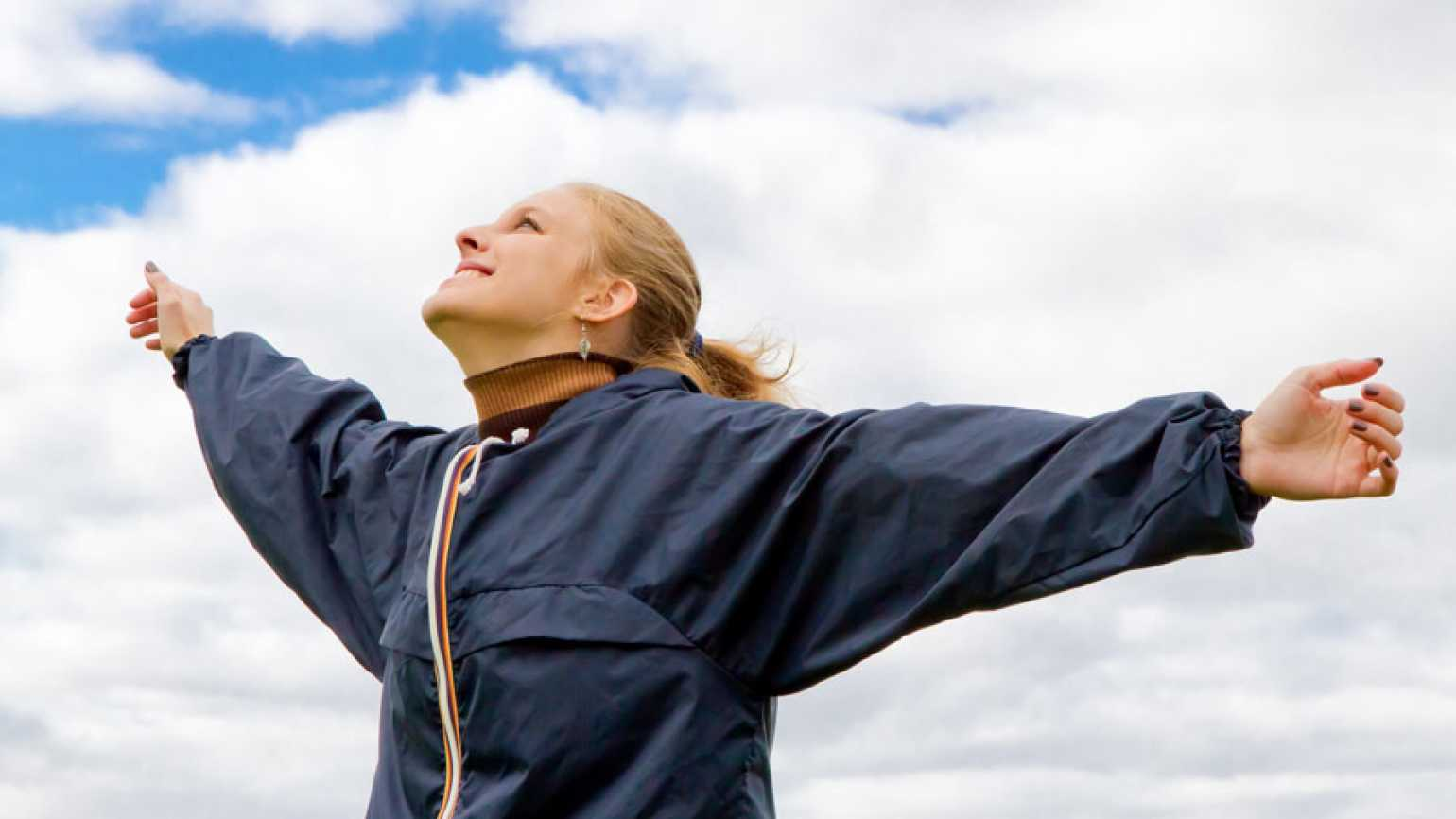 A smiling woman stands, arms spread, gazing up at the sky