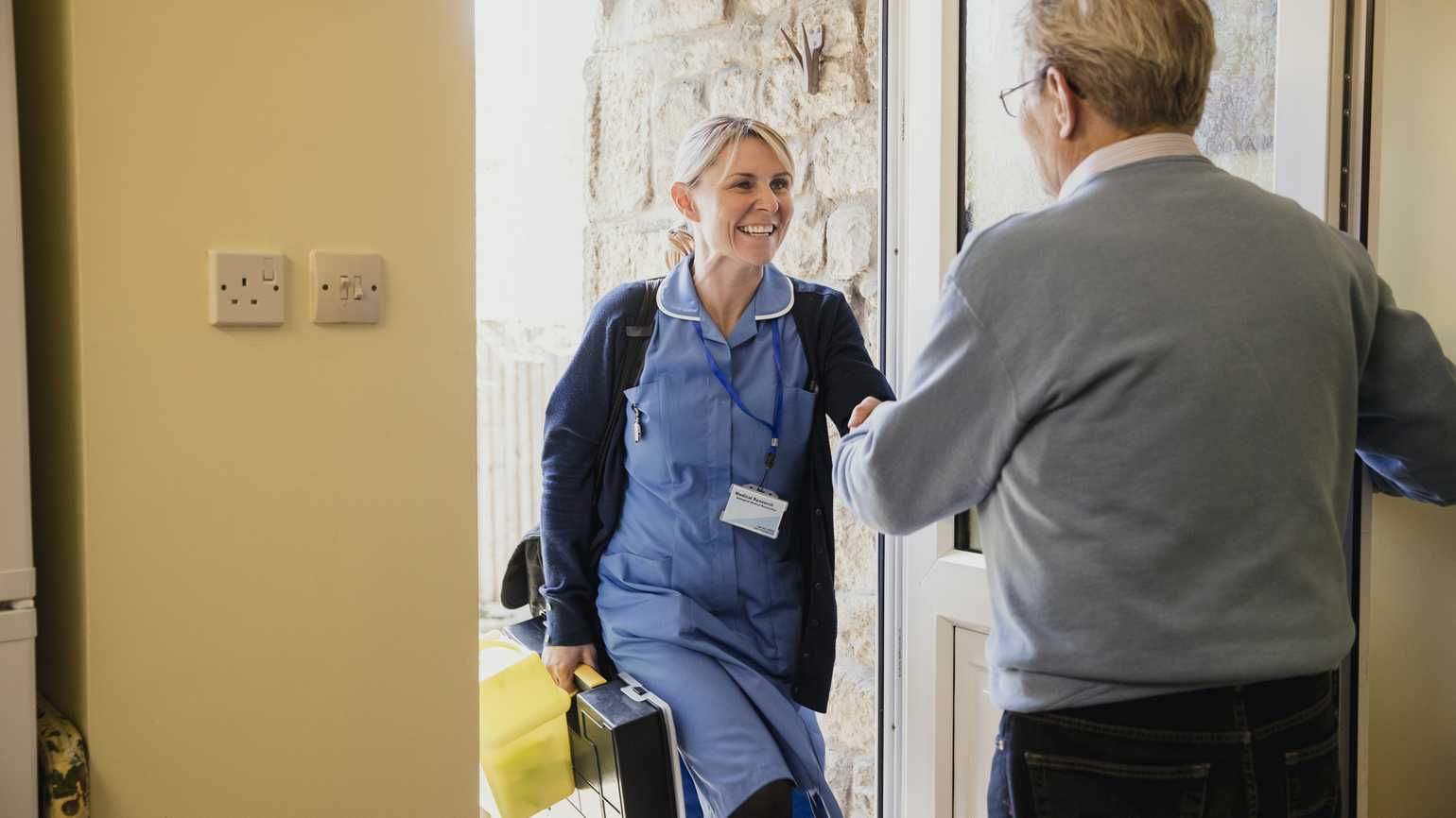 A home health aide at the doorstep of someone's home.