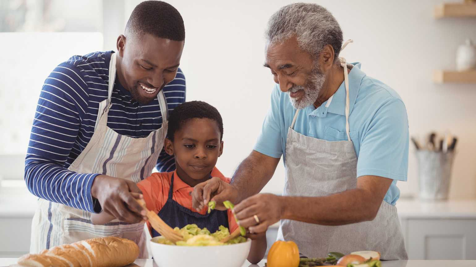 Happy multi-generation family preparing food in kitchen at home