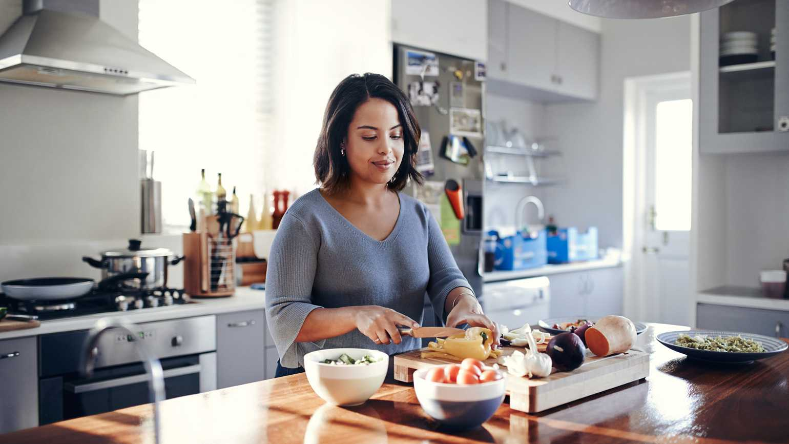 A young mother chopping vegetables to eat healthier.