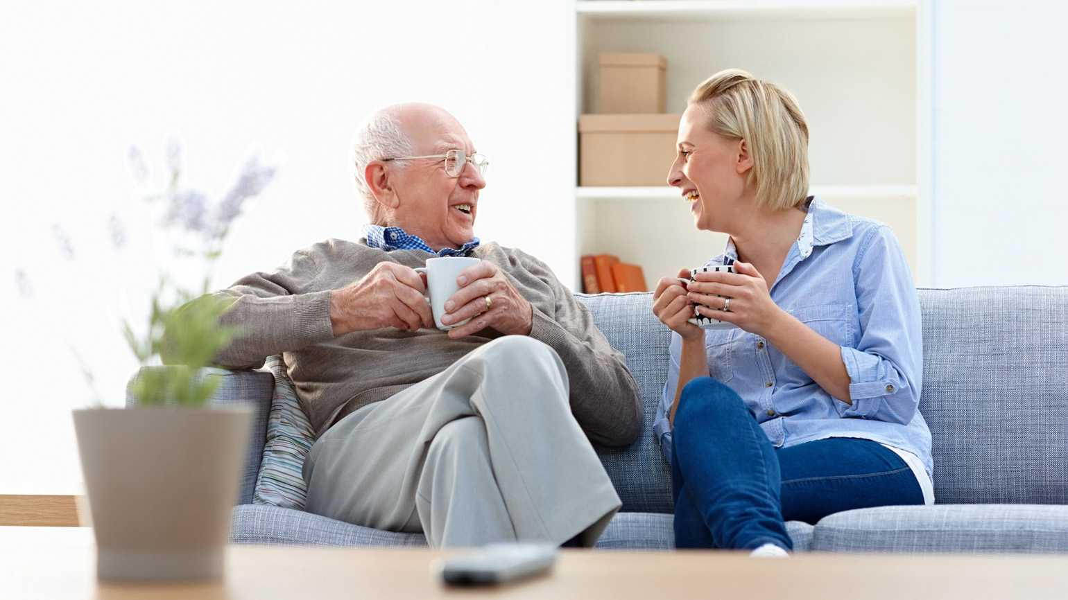 A senior father and his caregiver daughter having a laugh in their home.