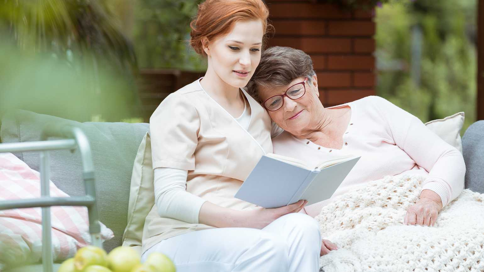 A hospice nurse reading to a senior patient outside.