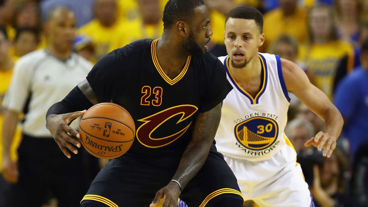Golden State's Stephen Curry closely guards Cleveland star LeBron James