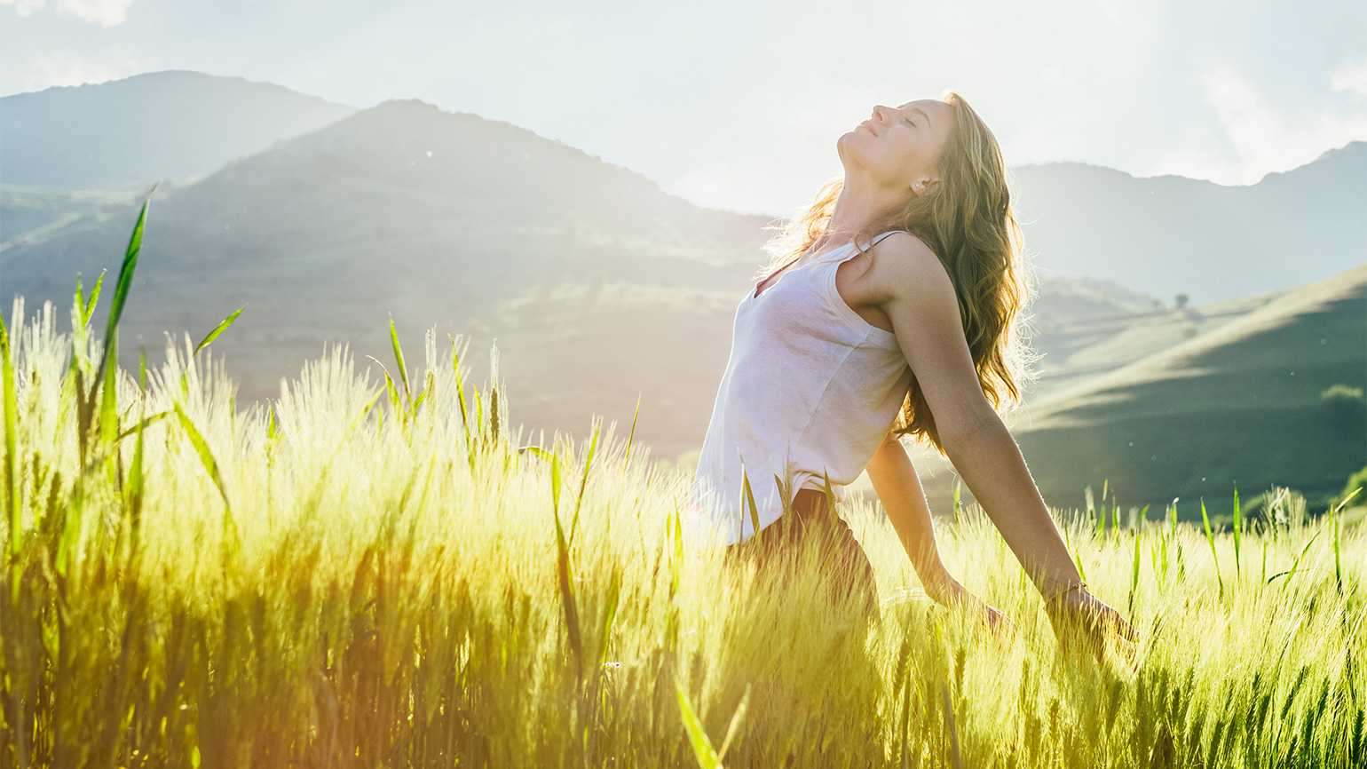 A woman soaks in the warm sun of a mountain meadow