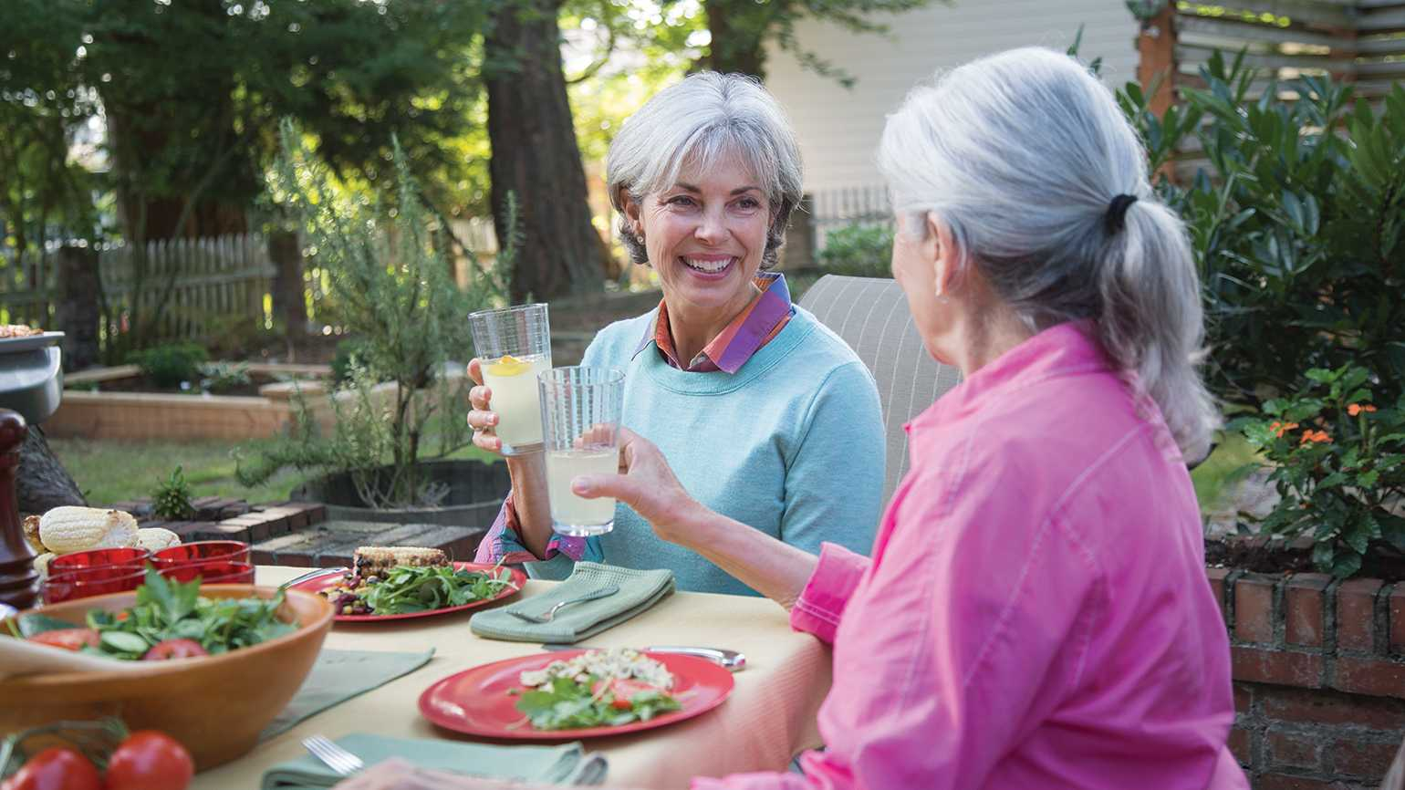 Two female friends enjoy a glass of lemonade together on a warm summer evening