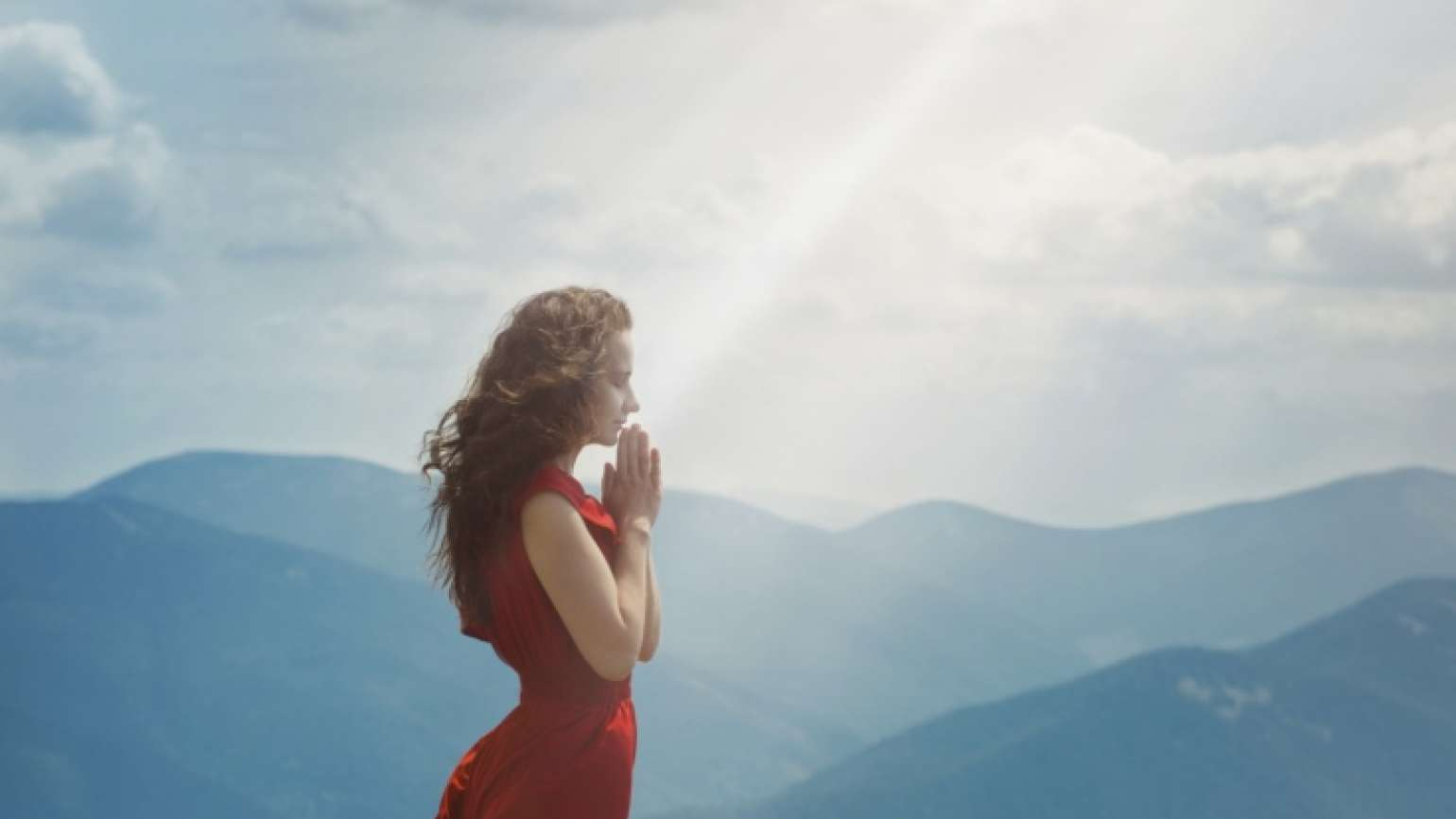Woman praying in a ray of glorious light
