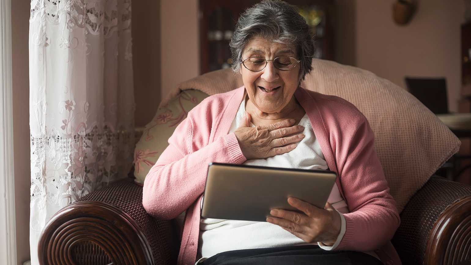 A senior women chats with family on her tablet