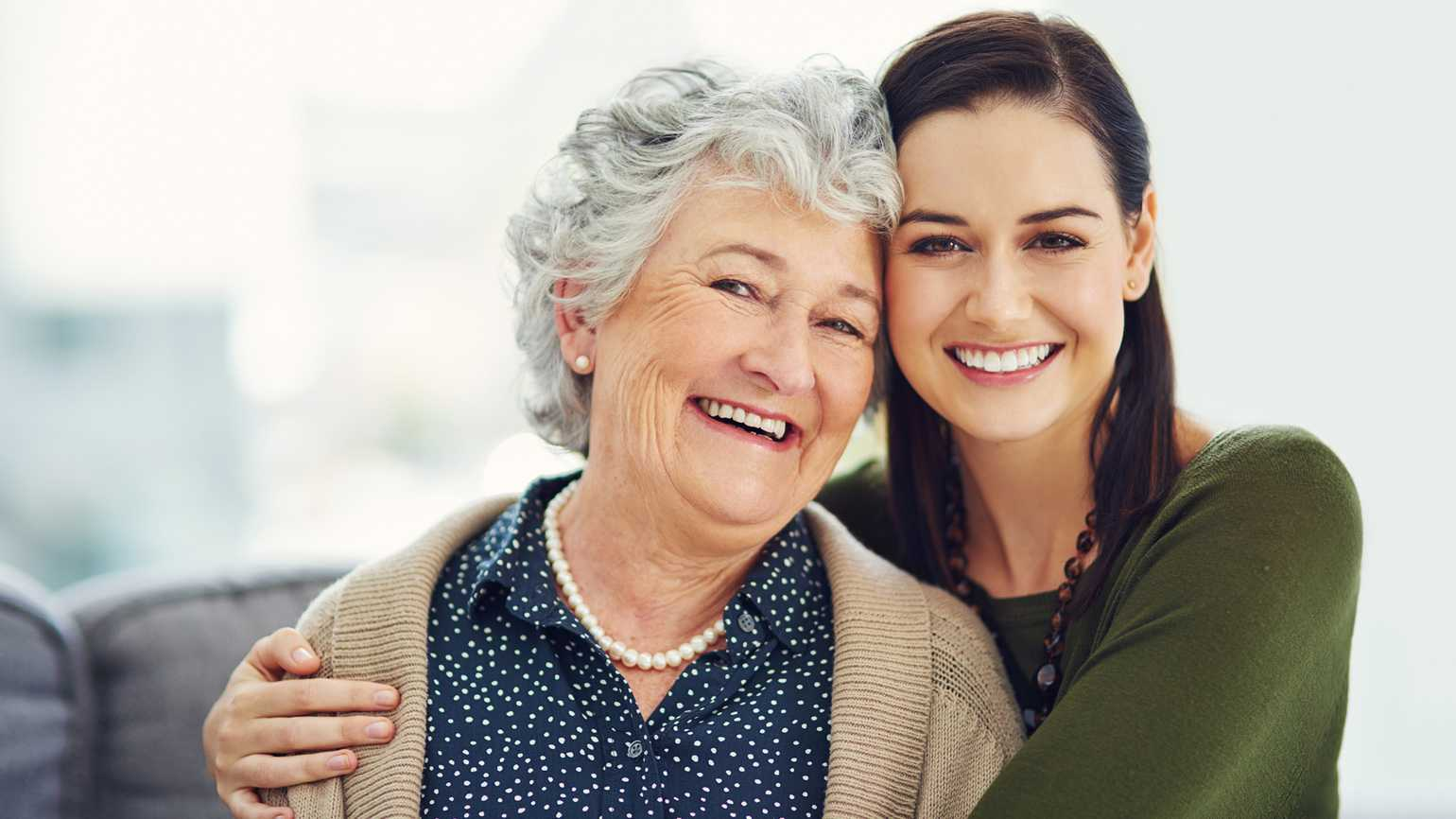 Portrait of a happy young woman spending time with her mom at home.