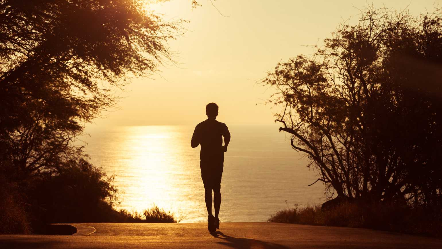 A silhouette of a man going for a morning run.