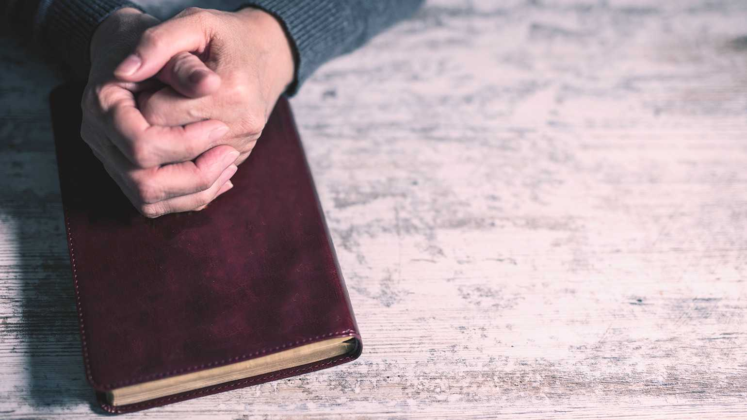 A man's hands rest in prayer upon a Bible