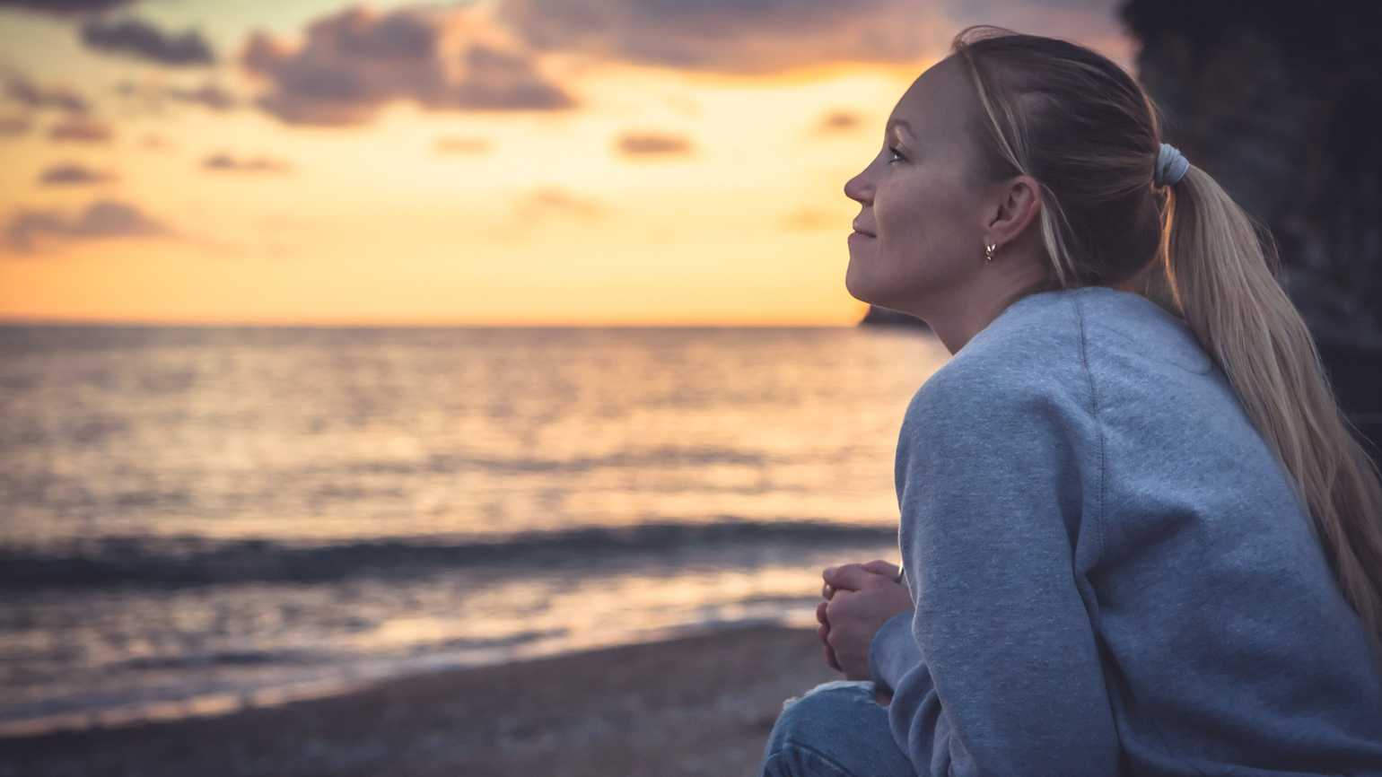 Smiling woman looking with hope into horizon during sunset at beach