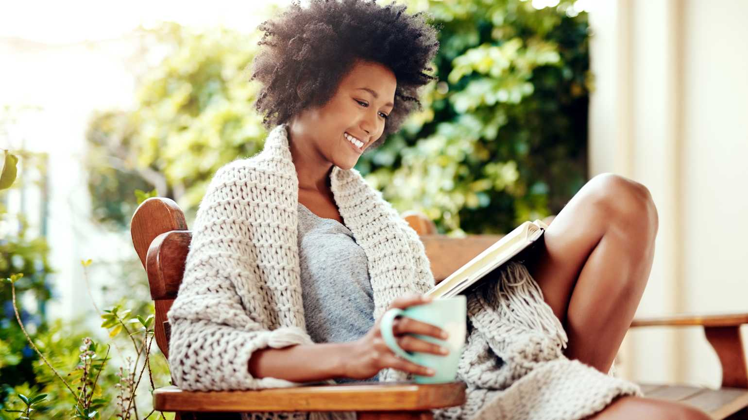 Shot of a young woman relaxing with coffee and a book at home.