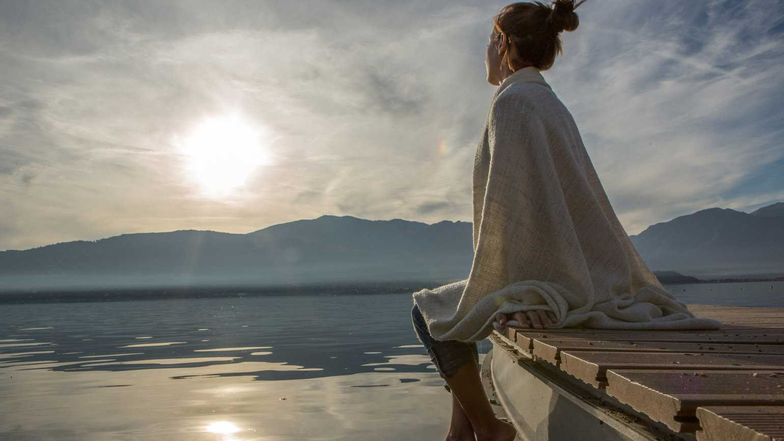 A woman sitting on the dock in deep reflection as the sun rises.