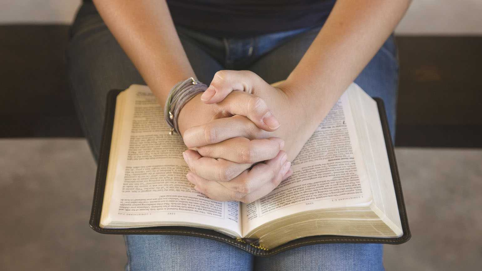 A teenage girl praying with the Bible open.