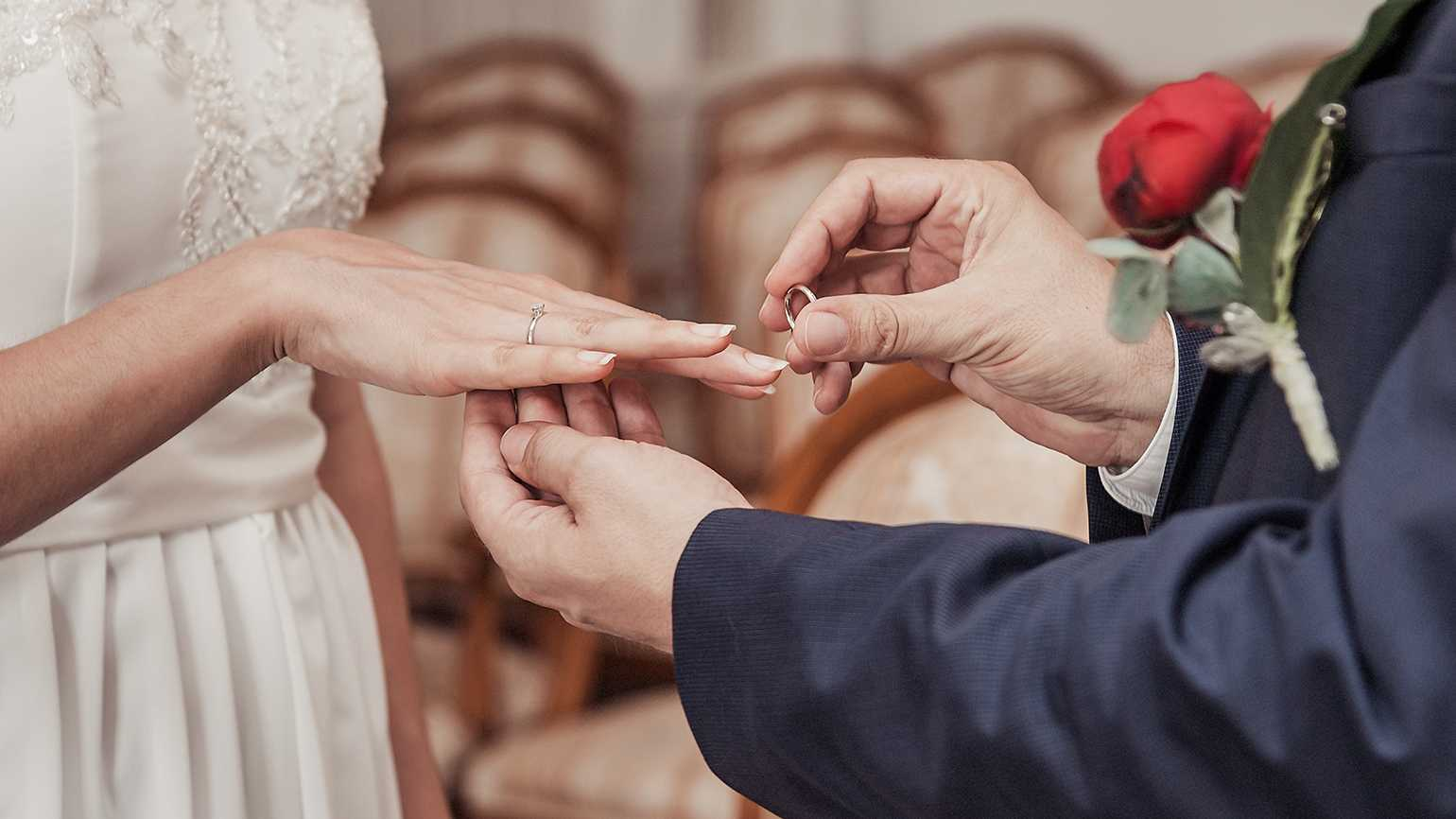 A mature couple exchanges rings during their wedding ceremony
