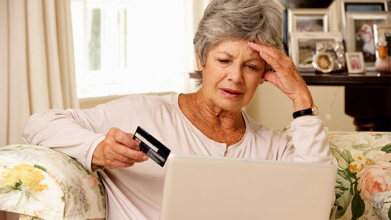 A senior looks with concern at a credit report on her laptop