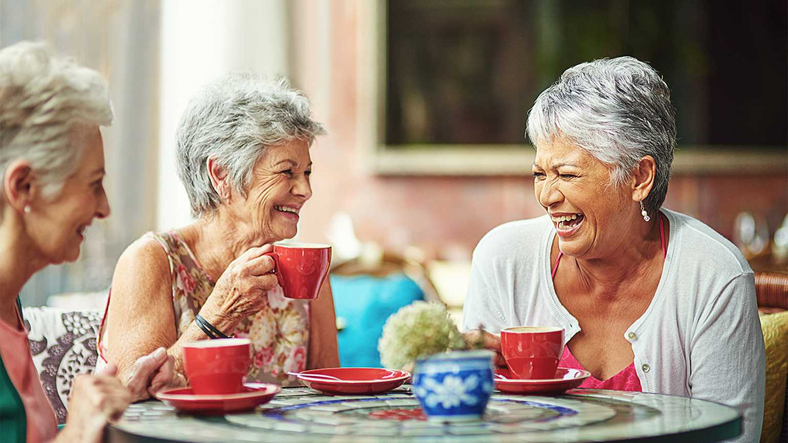 Senior women laughing over coffee