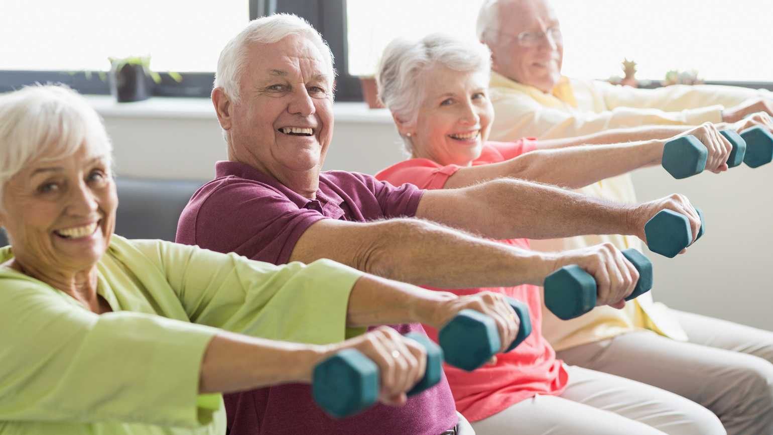 A group of enthusiastic senior citizens doing weight training.