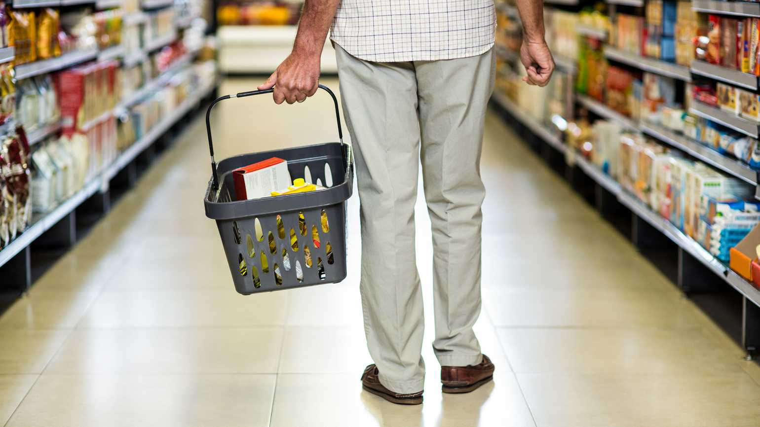 A senior man walking down a grocery aisle with a shopping basket full of items.