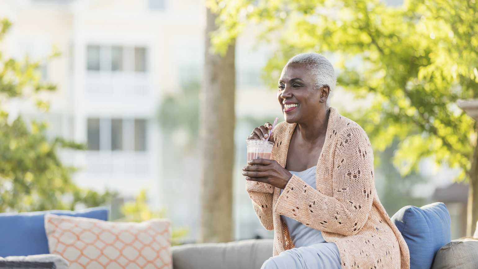 A woman in her golden years outside drinking a smoothie.