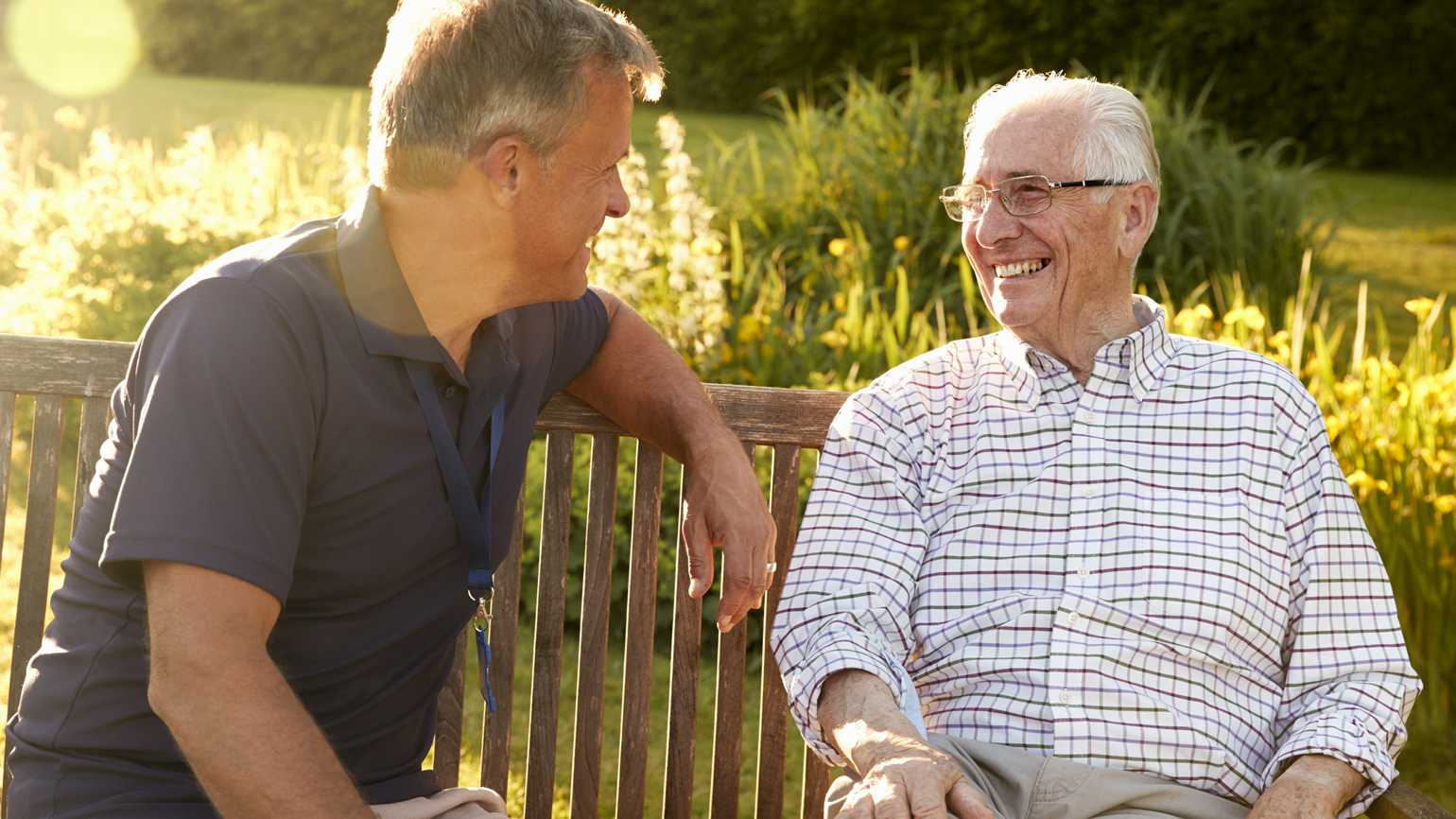 A senior father laughing with his son in conversation outside on a wooden bench.