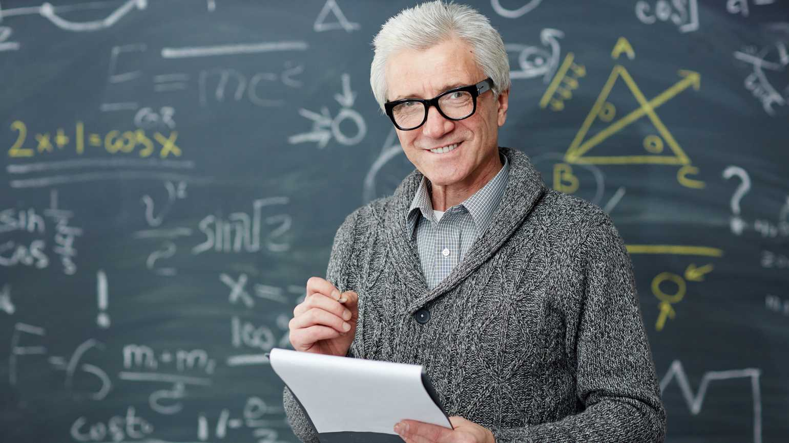 An older professor standing in front of a blackboard with math equations.