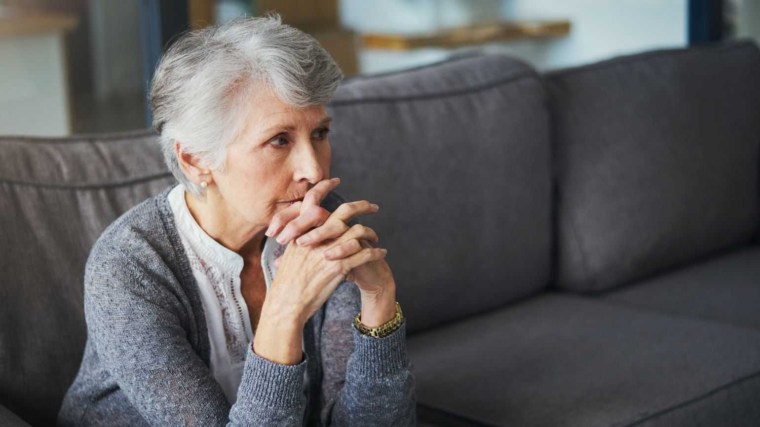 Woman sit on couch looking pensive