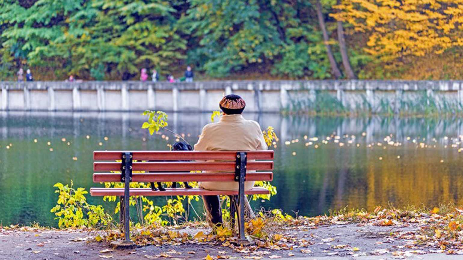 A woman sitting alone on a bench at a park on a crisp Autumn day.