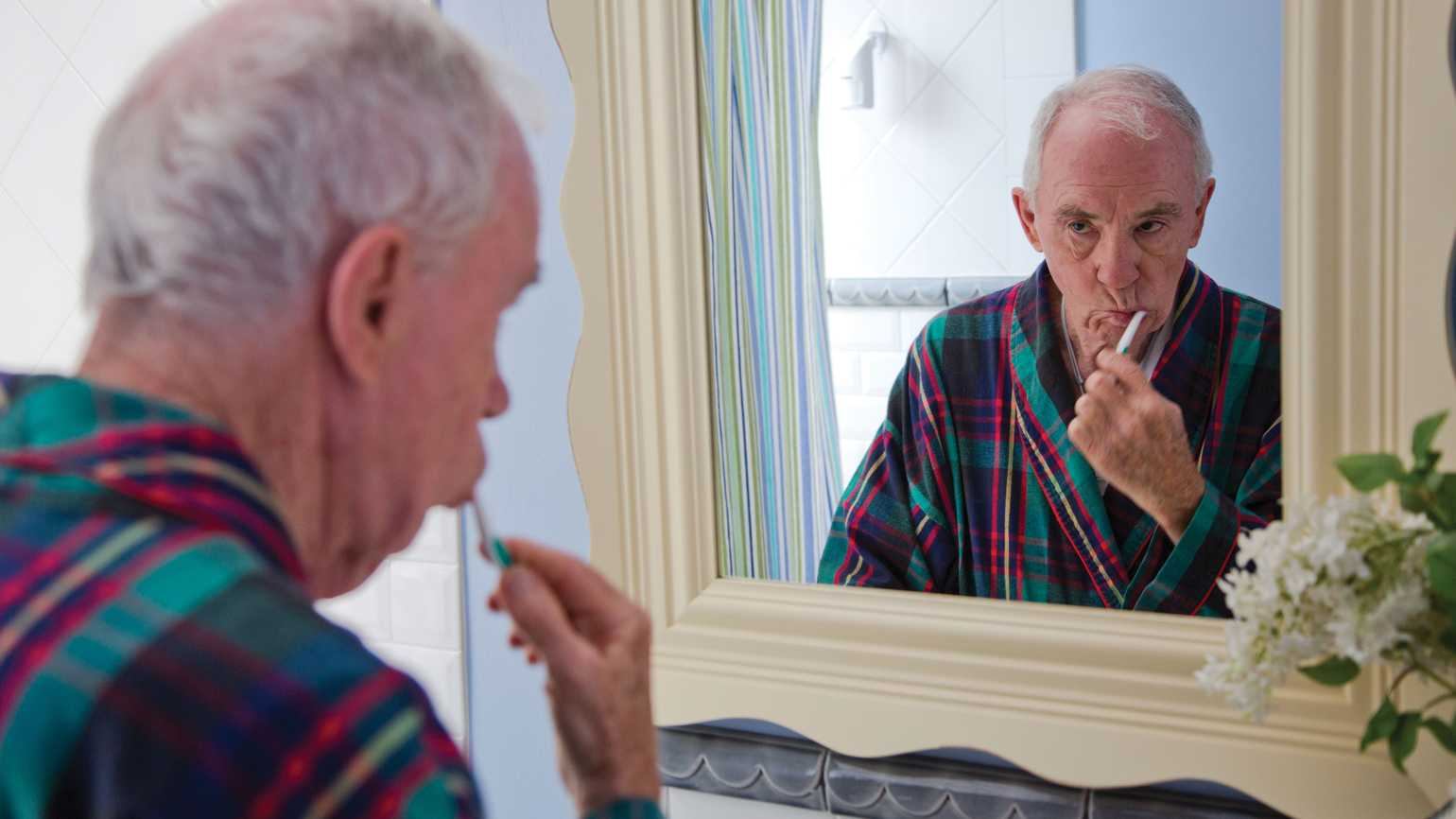 A senior citizen brushing his teeth while looking at his reflection in the bathroom mirror.