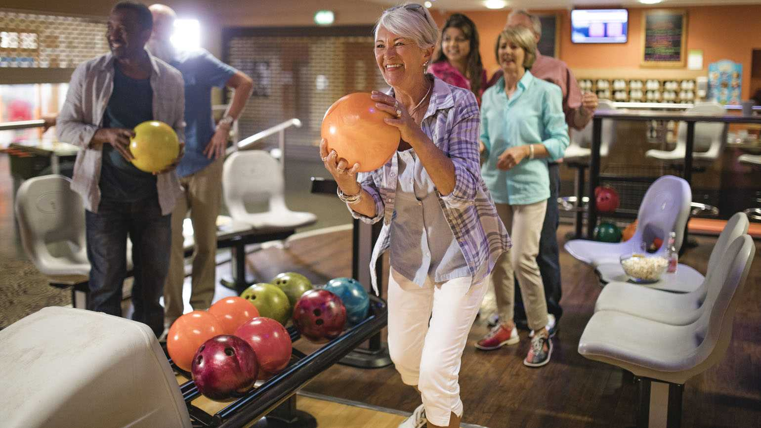 A woman bowling with friends.
