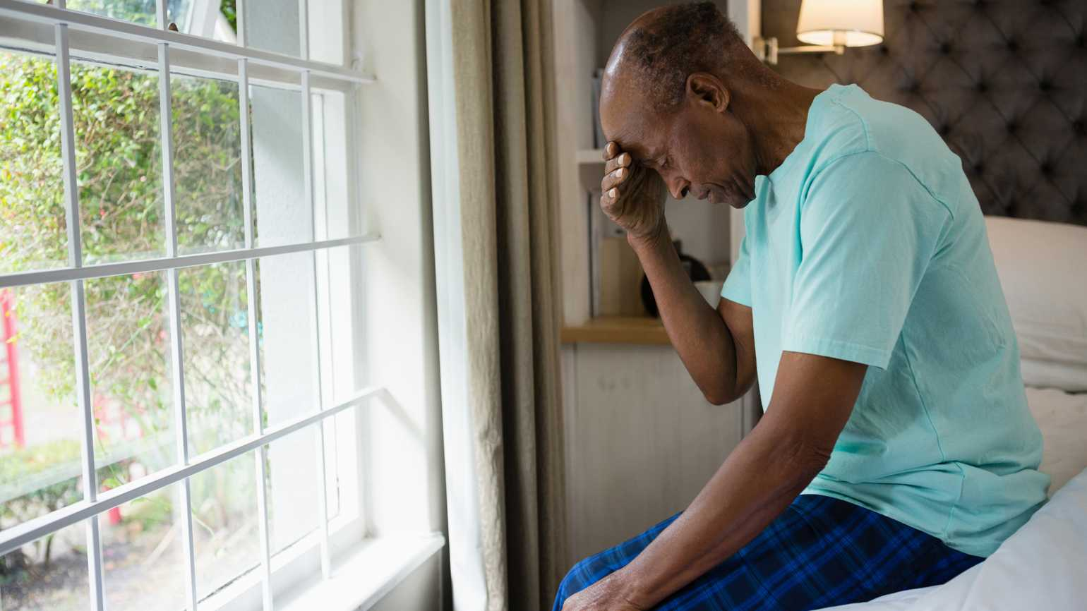 Side view of sad senior man sitting on bed by window in bedroom at home