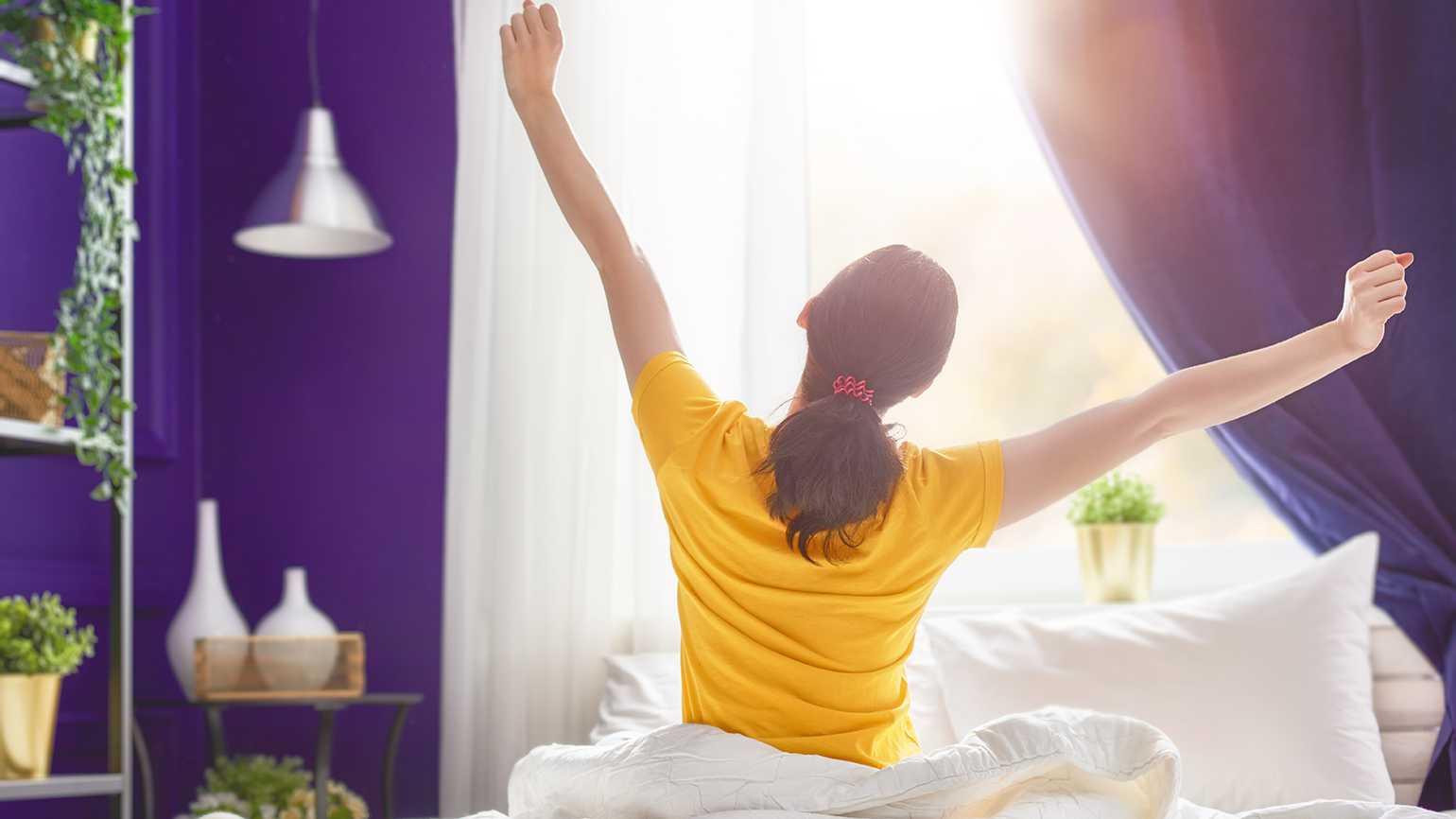 A young woman stretches as she welcomes a new day