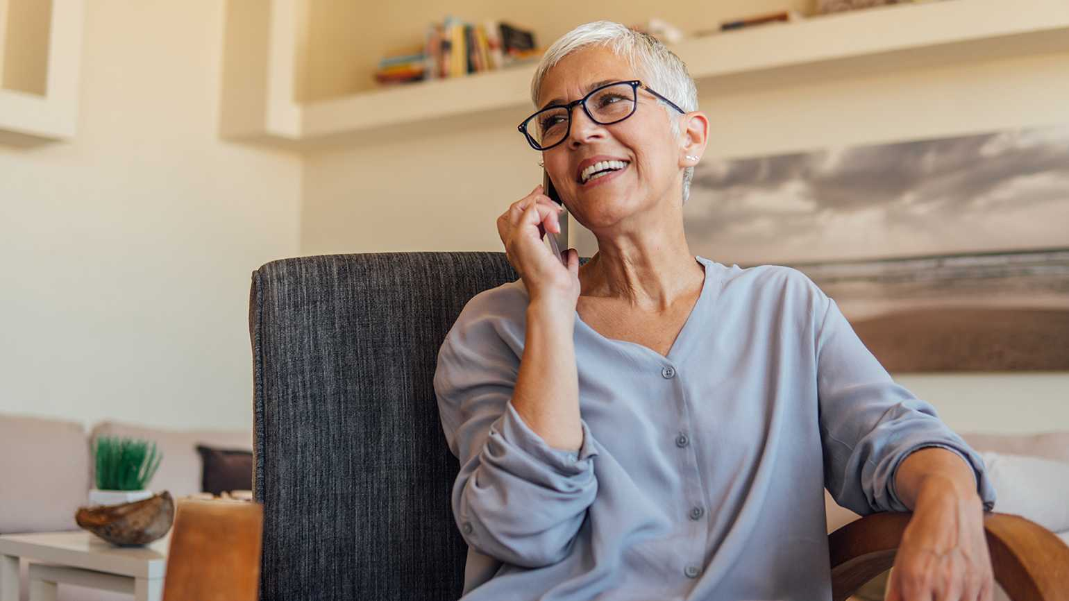 A woman speaks on the phone with a loved one she provides care for