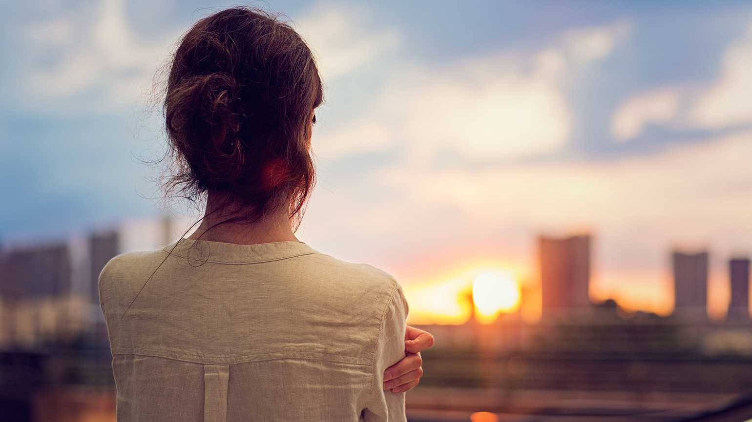A woman gazes out over a city skyline at sunrise