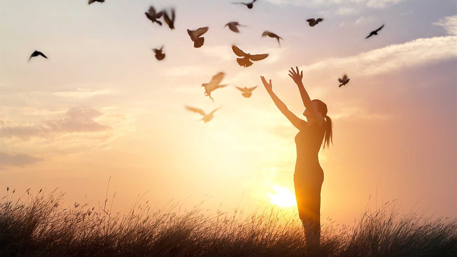 A woman with arms upraised at sunrise, a flock of doves flying around her