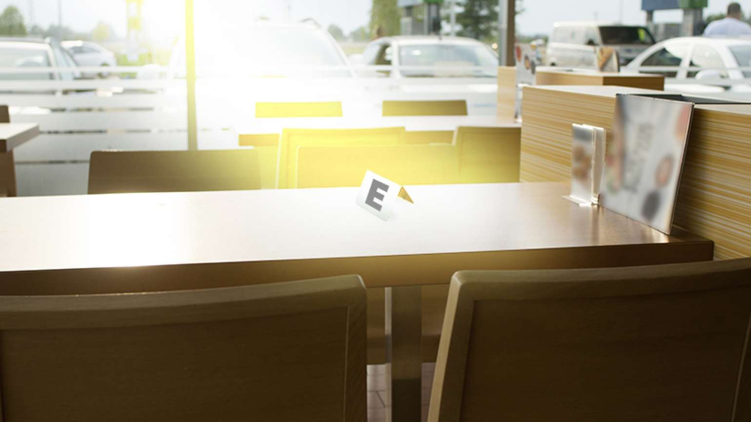 A table with a sign on it, lit by sunlight.