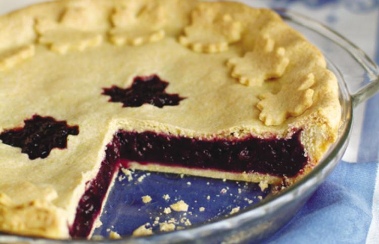 wild blueberry-maple pie with a cornmeal crust, one slice cut out of it