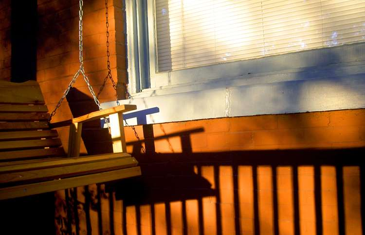 A wooden swing sways in the dappled sunlight of a porch.