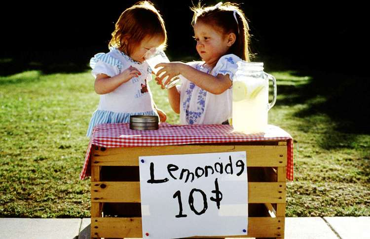 Two adorable little girls operate a lemonade stand on a warm summer day.
