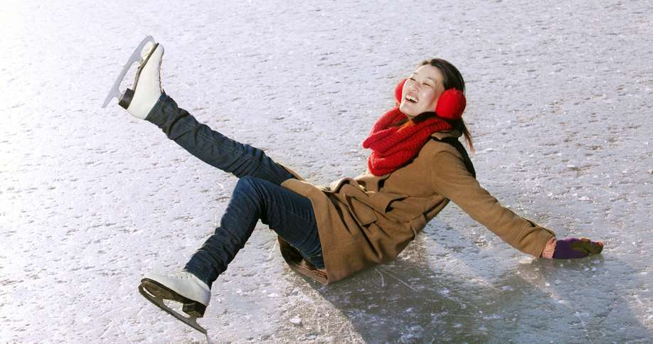 A good-natured woman takes a spill while ice skating in stride.