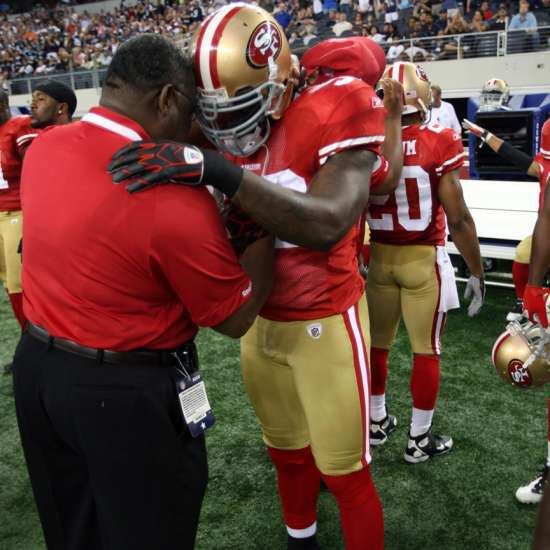 Smith prays with Patrick Willis during a 2009 preseason game against the Dallas Cowboys in Arlington, Texas.