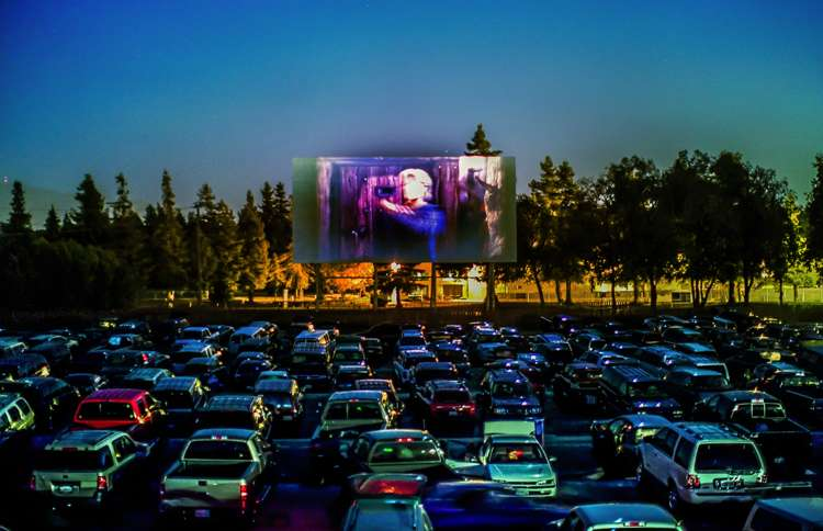 Row after row of families in cars enjoy a movie at their local drive-in.